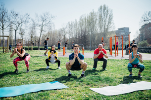 Calisthenics class at outdoor gym, women and men practicing yoga squatting poseの写真素材 [FYI03622982]