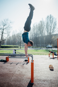 Calisthenics at outdoor gym, young man doing handstand on parallel barsの写真素材 [FYI03623019]