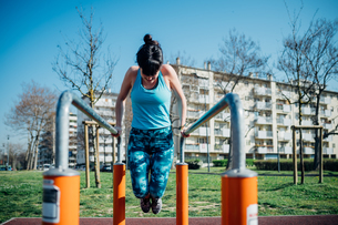 Calisthenics class at outdoor gym, young woman doing push ups on parallel barsの写真素材 [FYI03623023]