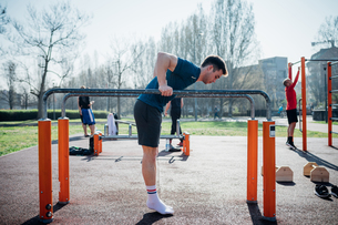 Calisthenics at outdoor gym, young man preparing to use parallel bars, full lengthの写真素材 [FYI03623024]