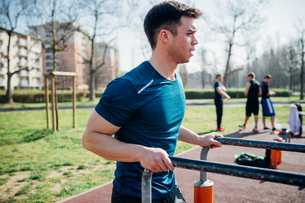Calisthenics at outdoor gym, young man preparing to use parallel barsの写真素材 [FYI03623025]