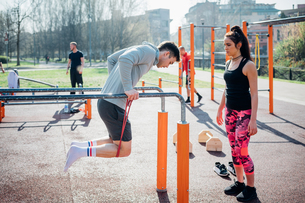 Calisthenics at outdoor gym, trainer watching young man on parallel barsの写真素材 [FYI03623036]