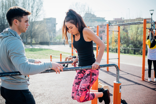Calisthenics at outdoor gym, trainer watching young woman on parallel barsの写真素材 [FYI03623039]