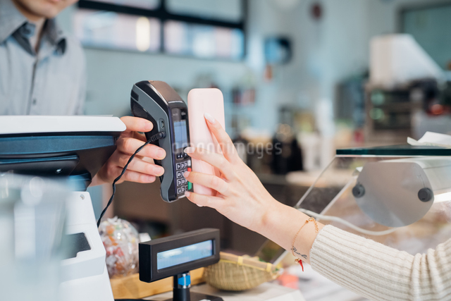 Young businesswoman making smartphone payment at cafe counter, croppedの写真素材 [FYI03623063]