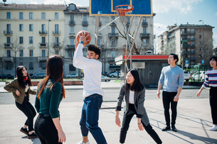 Young female and male adult friends playing basketball on city courtの写真素材 [FYI03623105]