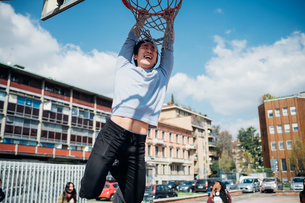 Young man hanging from basketball hoop at city basketball courtの写真素材 [FYI03623106]