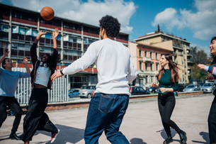 Young female and male adult friends playing basketball on city courtの写真素材 [FYI03623107]