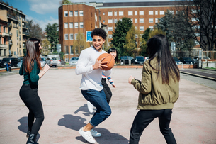 Young female and male adult friends playing basketball on city courtの写真素材 [FYI03623108]