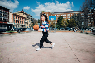 Young woman playing basketball on city basketball courtの写真素材 [FYI03623110]
