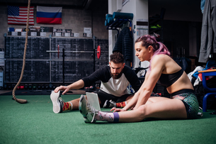 Young woman and man training together in gym, sitting on floor doing warm ups and looking at laptopの写真素材 [FYI03623168]