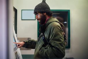 Bearded young man using cash machineの写真素材 [FYI03623181]