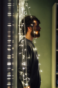 Bearded young man standing between string of decorative lightsの写真素材 [FYI03623183]