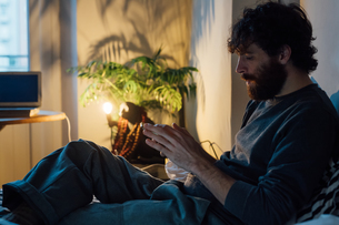 Bearded young man using smartphone in bedの写真素材 [FYI03623186]