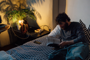 Bearded young man reading book in bedの写真素材 [FYI03623187]