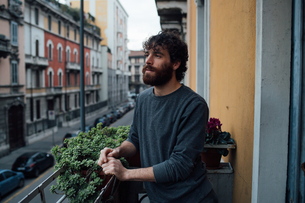 Bearded young man in deep thought on balconyの写真素材 [FYI03623193]