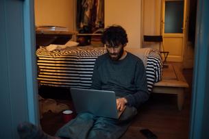 Bearded young man using laptop in bedroomの写真素材 [FYI03623196]