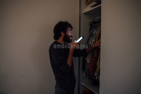 Bearded young man talking on smartphone in front of wardrobeの写真素材 [FYI03623199]