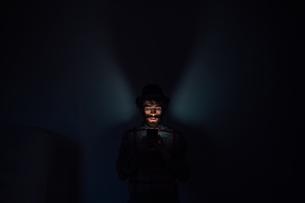 Bearded young man using smartphone in dark roomの写真素材 [FYI03623200]