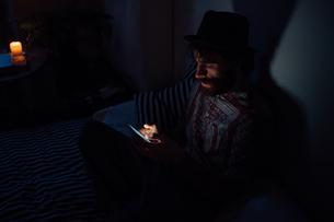 Bearded young man using smartphone in dark roomの写真素材 [FYI03623201]
