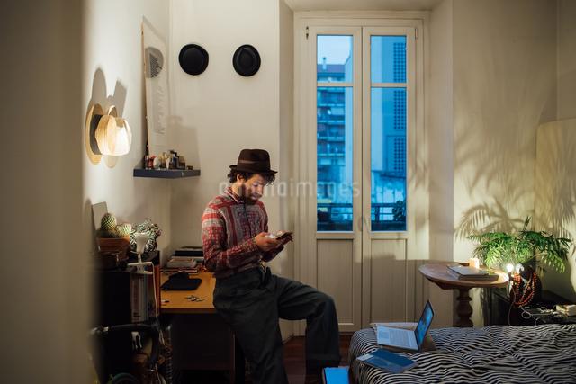 Bearded young man using smartphone on bedroom tableの写真素材 [FYI03623204]