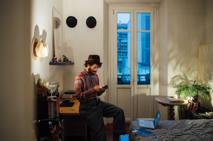 Bearded young man using smartphone on bedroom tableの写真素材 [FYI03623204]