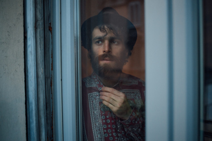 Bearded young man in deep thought by windowの写真素材 [FYI03623209]