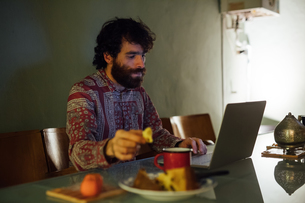 Bearded young man having breakfast, using laptop at homeの写真素材 [FYI03623210]