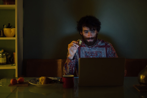 Bearded young man having breakfast, using laptop at homeの写真素材 [FYI03623212]