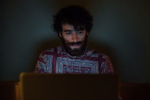 Bearded young man using laptop at homeの写真素材 [FYI03623213]