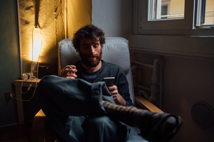 Bearded young man smoking, using smartphone at homeの写真素材 [FYI03623215]