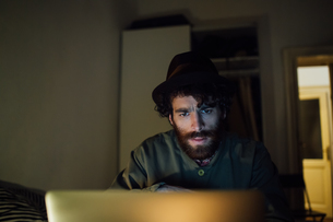 Bearded young man using laptop at homeの写真素材 [FYI03623220]