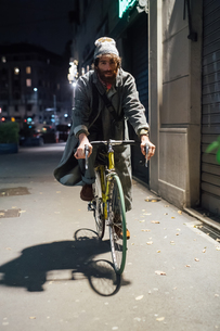 Bearded young man riding bicycle on pavementの写真素材 [FYI03623231]