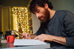 Bearded young man using smartphone and reading at homeの写真素材 [FYI03623236]