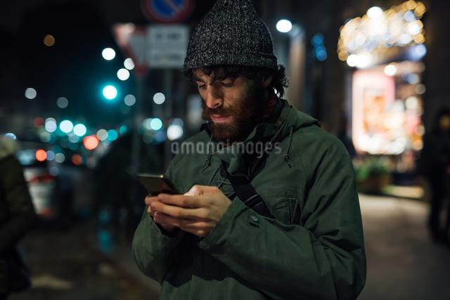 Bearded young man using smartphone on streetの写真素材 [FYI03623241]