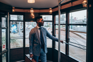 Businessman travelling on tram in cityの写真素材 [FYI03623385]