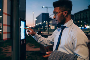 Businessman using digital information system at bus stop, Milano, Lombardia, Italyの写真素材 [FYI03623403]