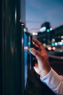 Businessman using digital information system at bus stopの写真素材 [FYI03623404]