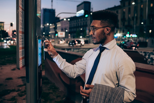 Businessman using digital information system at bus stop, Milano, Lombardia, Italyの写真素材 [FYI03623405]