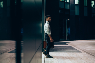 Businessman leaving office building, Milano, Lombardia, Italyの写真素材 [FYI03623424]