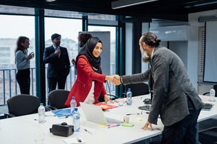 Business partners shaking hands at meeting in officeの写真素材 [FYI03623470]