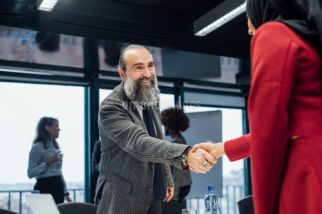 Business partners shaking hands at meeting in officeの写真素材 [FYI03623471]