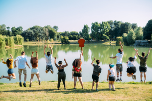 Group of friends jumping in front of lake in parkの写真素材 [FYI03623692]