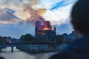Man watching Notre-Dame de Paris fire from far, Paris, Ile-de-France, Franceの写真素材 [FYI03623712]