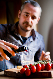 Man drinking wine and eating mediterranean food in cafeの写真素材 [FYI03623738]