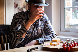 Man drinking wine and eating mediterranean food in cafeの写真素材 [FYI03623739]