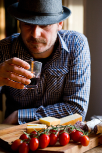 Man drinking wine and eating mediterranean food in cafeの写真素材 [FYI03623742]