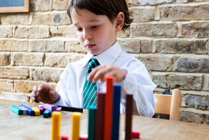 Boy in school uniform playing with colour sticks at homeの写真素材 [FYI03623744]