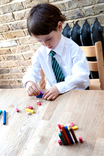 Boy in school uniform playing with colour sticks at homeの写真素材 [FYI03623745]