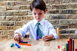 Boy in school uniform playing with colour sticks at homeの写真素材 [FYI03623751]