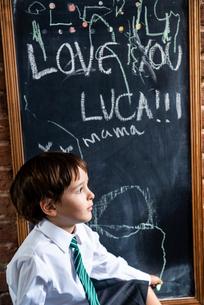 Boy in school uniform beside blackboard at homeの写真素材 [FYI03623753]